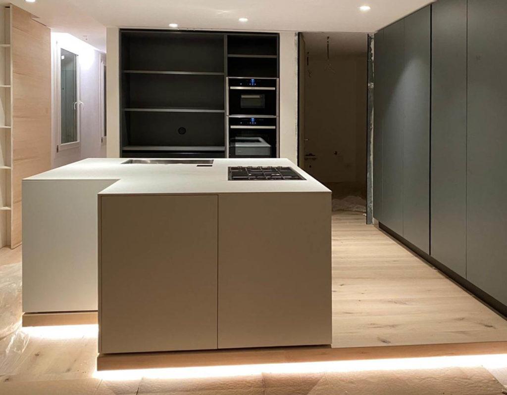 Residenza privata a Desenzano: Design ICM - Cucina con isola: l'anta opaca laccata bianco seta, abbinata al piano in Corian spessore 1.2, sviluppano un monolite operativo. Colonne laccate grigio opaco silice.